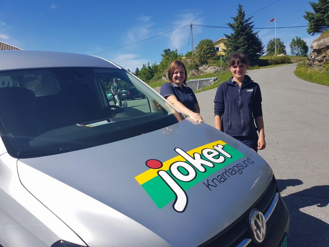 To joker-ansatte foran den nye firmabilen
